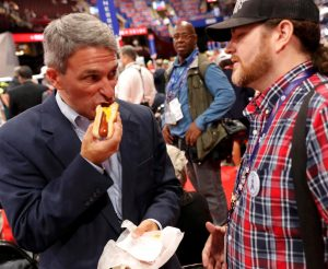 Former Virginia Attorney General Ken Cuccinelli sneaks in a quick hot dog on the floor of the Republican National Convention as he discusses a controversial fight over the RNC rules with a delegate. (Reuters/Jonathan Ernst)