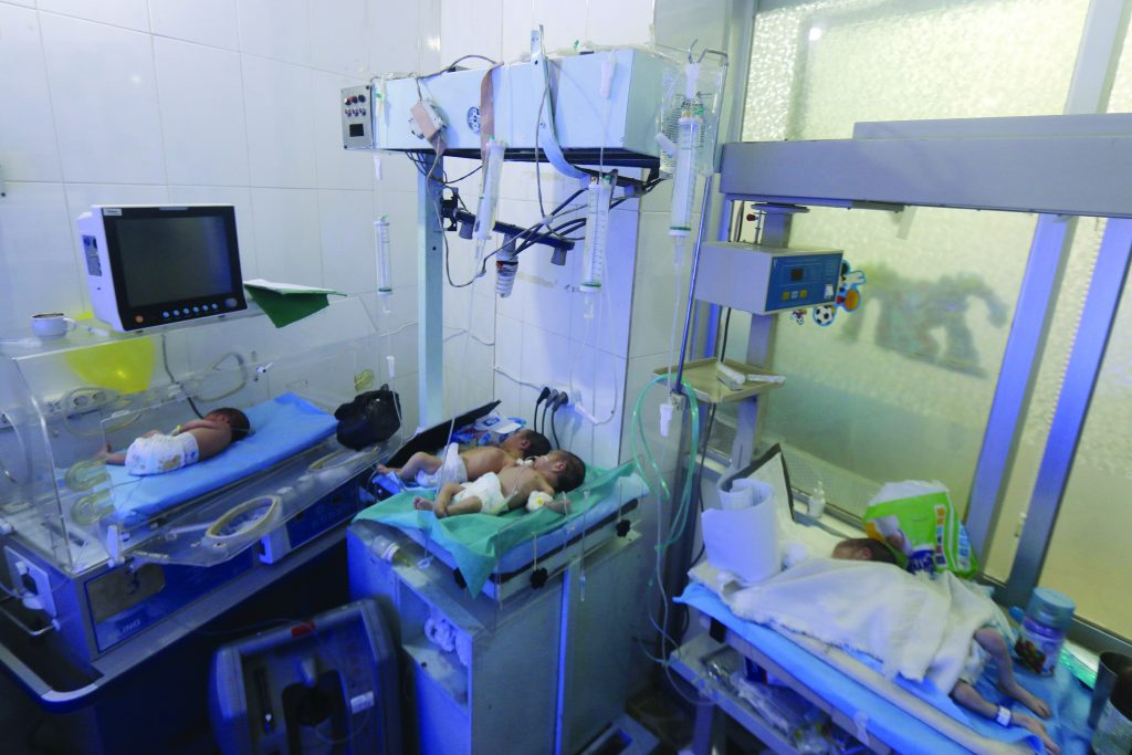 Babies are seen inside a nursery at a children's hospital that was partially damaged from recent airstrikes, in a rebel-held area of Aleppo,Syria. (Abdalrhman Ismail/Reuters)