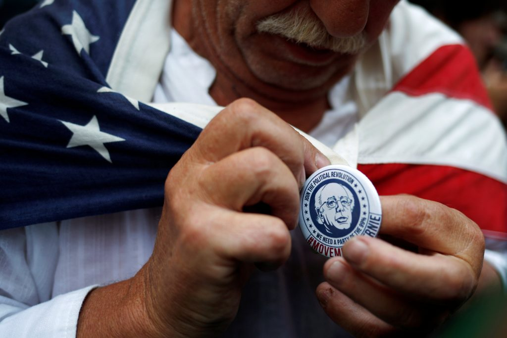 A Bernie Sanders supporter places a Sanders pin with his image on his shirt before a protest march ahead of the 2016 Democratic National Convention in Philadelphia on Monday. (Reuters/Adrees Latif)