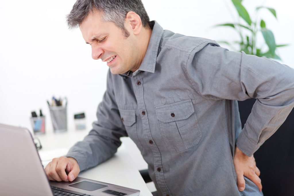Man having a back pain while sitting at the working desk.