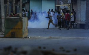 Kashmiri protesters run as a tear gas shell explodes near them as they clash with Indian troops in Srinagar, Indian-controlled Kashmir, last Sunday. (AP Photo/Mukhtar Khan)