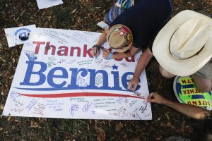 Bernie Sanders supporters write comments on a sign following a protest march through downtown Philadelphia on Sunday. (AP Photo/John Minchillo)
