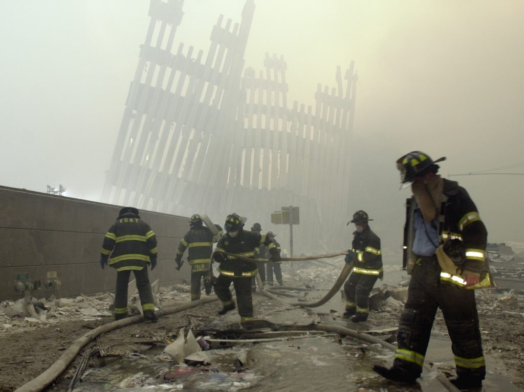 FILE - In this Sept. 11, 2001, file photo, firefighters work beneath the destroyed mullions, the vertical struts which once faced the soaring outer walls of the World Trade Center towers, after a terrorist attack on the twin towers in New York. White House and intelligence officials are deciding whether to declassify 28 pages of a congressional investigation into the Sept. 11 attacks. The still-secret chapter could answer or raise new questions about possible Saudi links to the attackers. (AP Photo/Mark Lennihan, File)
