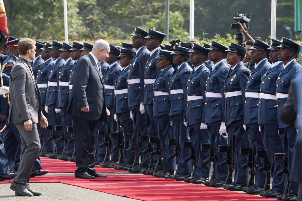 Israeli Prime Minister Benjamin Netanyahu, second from left, stops to talk with a soldier as he inspects a guard of honor at Nairobi State House in Nairobi, Kenya, Tuesday, July 5, 2016. Netanyahu is in Kenya as part of his four-nation tour of Africa. (AP Photo/Sayyid Abdul Azim)