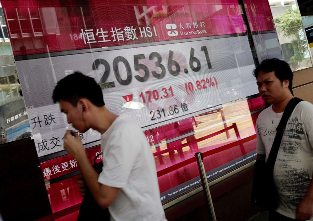 People walk past an electronic board showing Hong Kong stock index outside a local bank in Hong Kong, Friday, July 8, 2016. Asian shares mostly fell Friday, with investors cautious following the plunge in oil prices overnight and concerns that a correction in commodity prices is underway, and as they await the release of U.S. inflation and June non-farm payrolls data later in the day. (AP Photo/Vincent Yu)