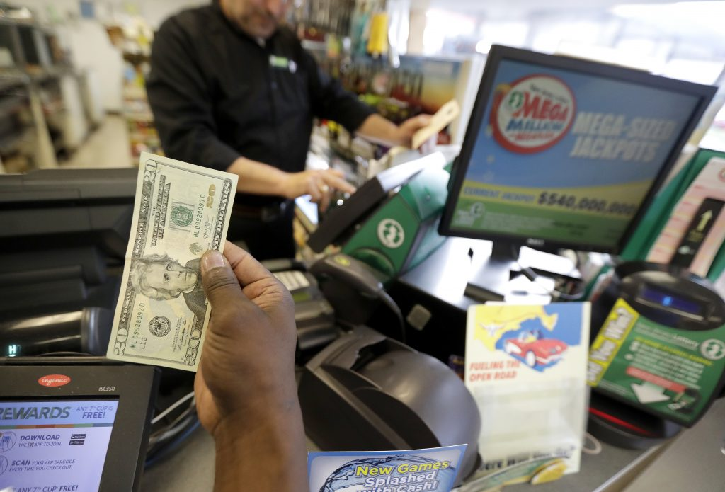 Chase Hardy buys lottery tickets at a 7-Eleven store, Friday, July 8, 2016, in Newark, N.J. The Mega Millions lottery jackpot for Friday's drawing has soared to over $500 million. (AP Photo/Julio Cortez)