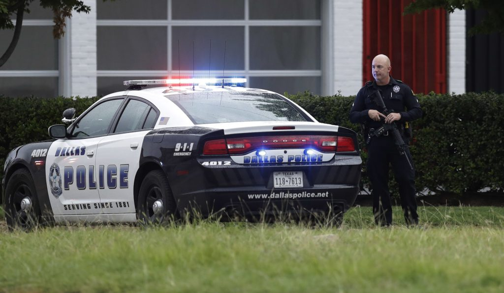 Dallas police tighten security at their headquarters after receiving an anonymous threat against law enforcement across the city Saturday, July 9, 2016, in Dallas. Security measures were heightened after a peaceful protest, over the recent shootings of black men by police, turned violent Thursday night when gunman Micah Johnson shot at officers, killing several and injuring others. (AP Photo/Eric Gay)