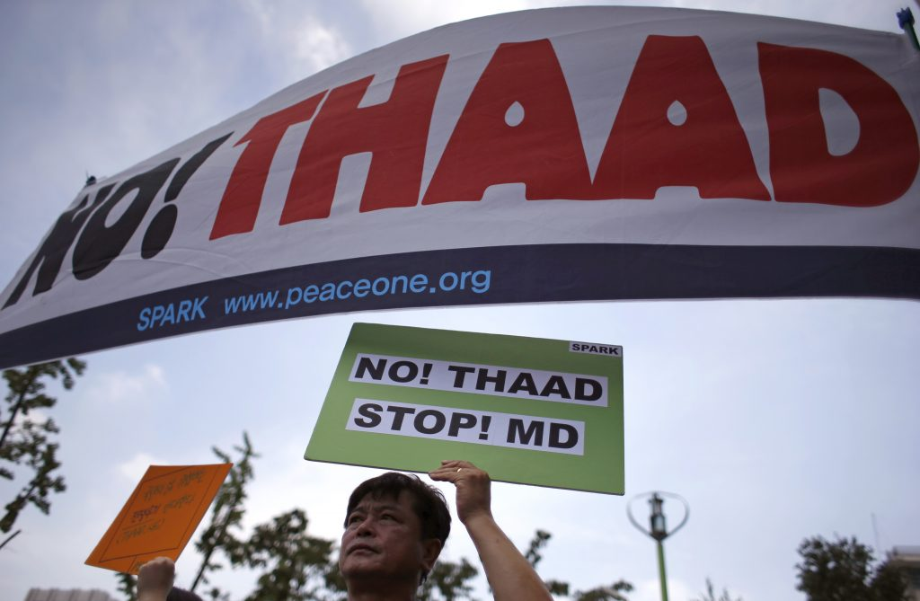 A South Korean man holds a sign during a rally to denounce deploying the Terminal High-Altitude Area Defense, or THAAD, near U.S. Embassy in Seoul, South Korea, Monday, July 11, 2016. Seoul and Washington launched formal talks on deploying the Terminal High-Altitude Area Defense, or THAAD, after North Korea conducted a nuclear test and a long-range rocket launch earlier this year. China, Russia and North Korea all say the THAAD deployment could help U.S. radars spot missiles in their countries. (AP Photo/Lee Jin-man)