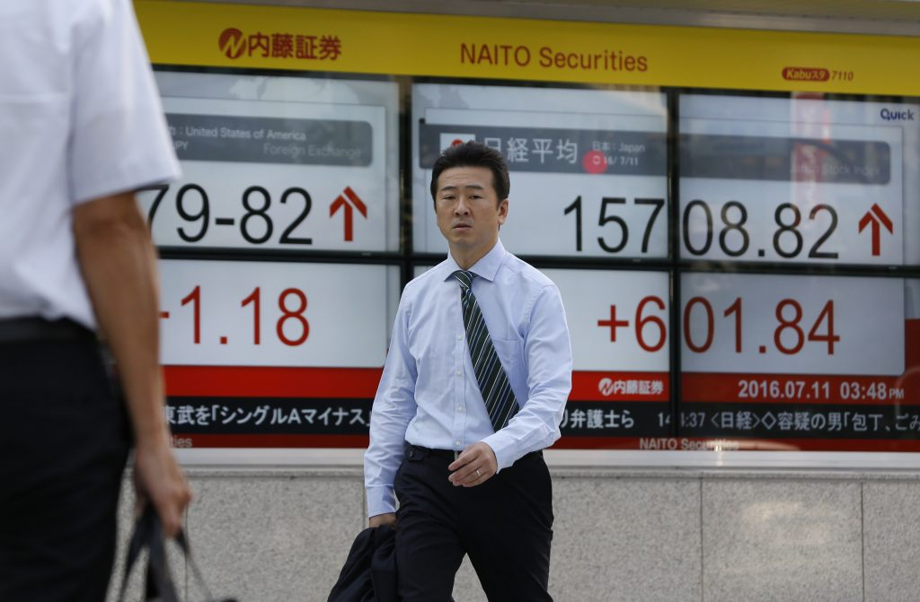 A man walks past an electronic stock indicator at a securities firm in Tokyo, Monday, July 11, 2016. Asian shares rose Monday after Wall Street rose on a strong U.S. employment report and as global investors recovered gradually from post-Brexit jitters. (AP Photo/Shizuo Kambayashi)