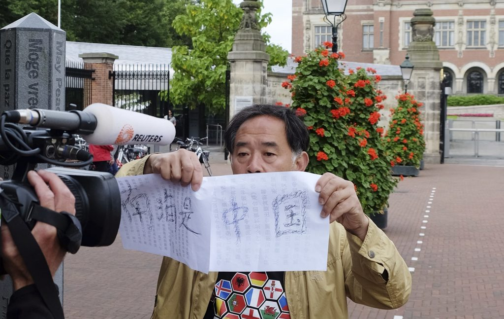 "A man holds up a handwritten sign in Chinese which says ""South Sea belongs to China"", in reference to the South China Sea, outside the Peace Palace in The Hague, Netherlands, on Tuesday, July 12, 2016, ahead of a ruling by the Permanent Court of Arbitration (PCA) on the dispute between China and the Philippines over the South China Sea. China has intensified the drumbeat of its opposition to an international tribunal's ruling expected Tuesday that could threaten its expansive claims in the South China Sea. (AP Photo/Mike Corder)"