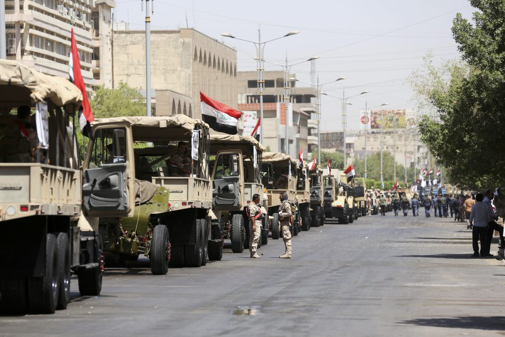 Iraqi army vehicles rehearse for a military parade in central Baghdad, on Tuesday. (AP Photo/Hadi Mizban)