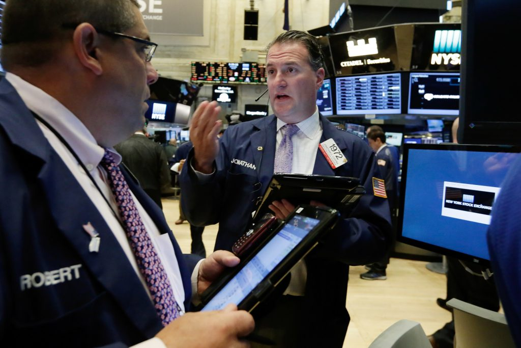 Traders Robert Oswald, left, and Jonathan Corpina converse as they work on the floor of the New York Stock Exchange on Wednesday. (AP Photo/Richard Drew)