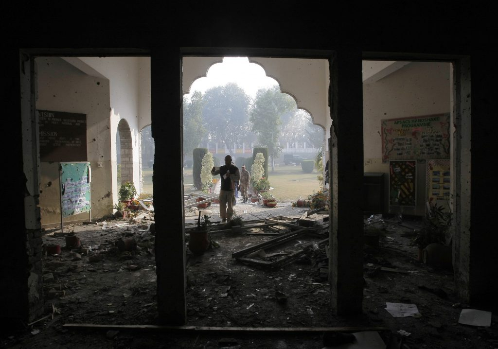 In this Dec. 17, 2014 photo, a Pakistani soldier inspects the Army Public School that was  attacked a day before by Taliban gunmen, in Peshawar, Pakistan. (AP Photo/B.K. Bangash, File)