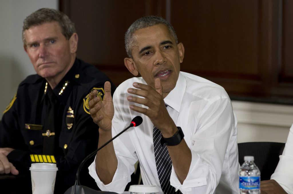 President Barack Obama, joined by Brittany Packnett, of the President's Taskforce on 21st Century Policing, right, and Terry Cunningham, President of the International Association of Chiefs of Police, left, speaks to media at the bottom of a meeting at the Eisenhower Executive Office Building on the White House complex in Washington, Wednesday, July 13, 2016, about community policing and criminal justice with a group made of activists, civil rights, faith, law enforcement and elected leaders. (AP Photo/Carolyn Kaster)