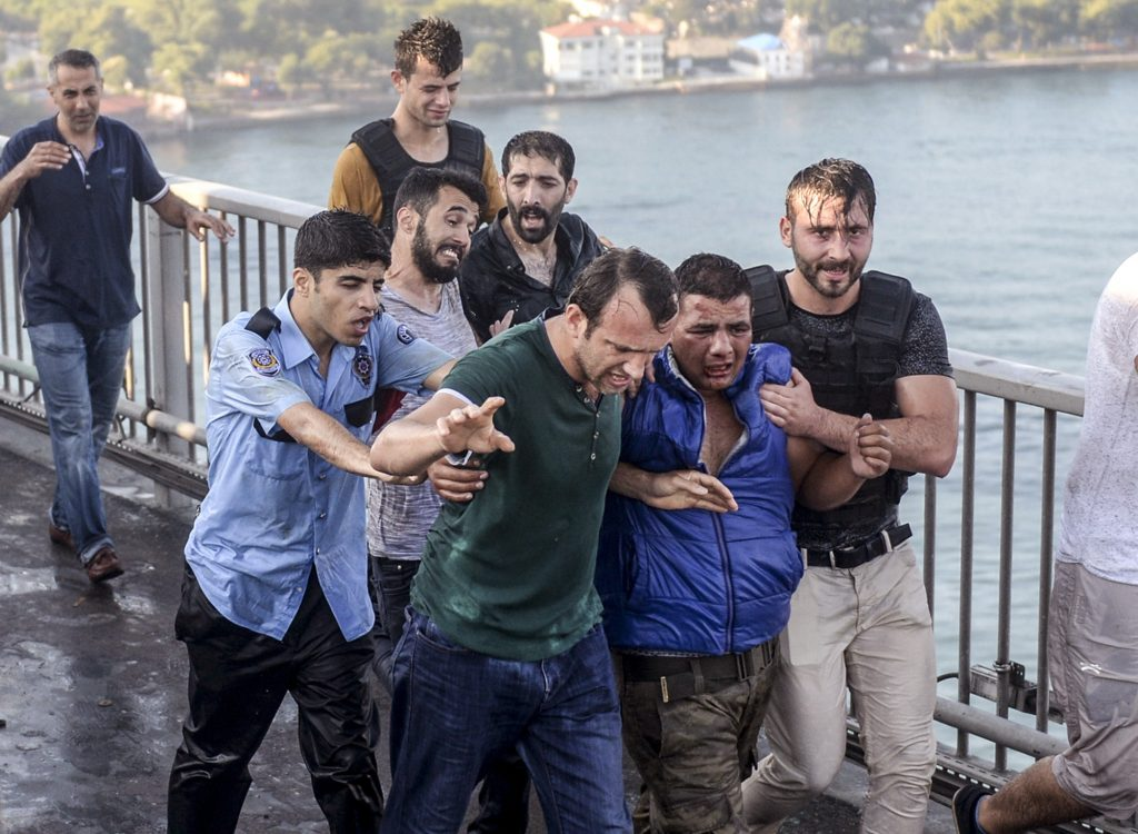 People apprehend a Turkish soldier that participated in the attempted coup, on Istanbul's Bosporus Bridge, Saturday, July 16, 2016. Turkish President Recep Tayyip Erdogan told the nation Saturday that his government was working to crush a coup attempt after a night of explosions, air battles and gunfire across the capital that left dozens dead and scores wounded. Government officials said the coup appeared to have failed as Turks took to the streets overnight to confront troops attempting to take over the country. (AP Photo/Selcuk Samiloglu)