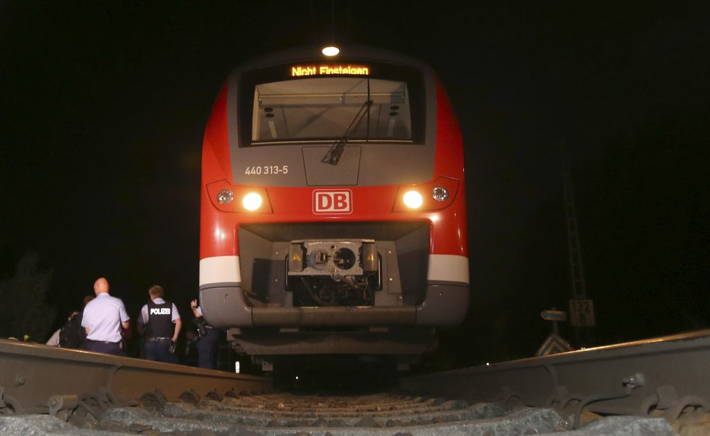 Police officers stand beside a train in Wuerzburg, southern Germany, Monday evening, after a 17-year-old Afghan armed with an ax and a knife attacked passengers aboard a regional train in southern Germany. (Karl-Josef Hildenbrand/dpa via AP)