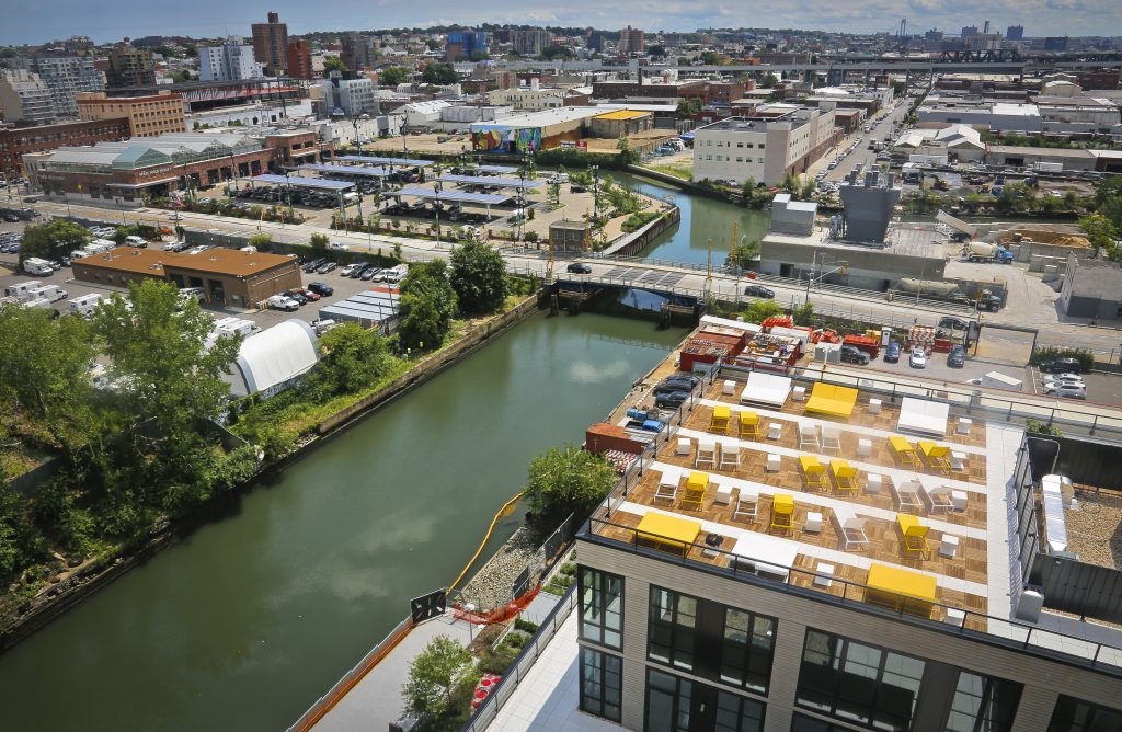 A view of Brooklyn's Gowanus Canal and the the rooftop lounge of the new 365 Bond Street apartments, right, a new development from Lightstone. (AP Photo/Bebeto Matthews)