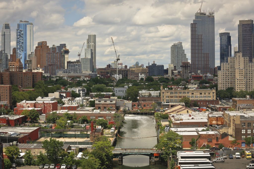 This Tuesday, July 5, 2016 photo shows a view of Brooklyn's Gowanus Canal from the rooftop of 363 Bond Street apartments, a new development from Lightstone, in New York. The canal is a Superfund site polluted with decades' worth of industrial waste and sewage, but the developer says the pending more than half a billion dollars cleanup of the toxic waterway hasn't deterred tenants from flocking to the building, where the rent for a one-bedroom apartment starts in the low $3,000s. (AP Photo/Bebeto Matthews)