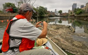 John Lipscomb, who in the last 16 years has been the patrol boat captain for Riverkeeper, the nonprofit watchdog organization dedicated to protecting the Hudson, makes photos of a sewage run-off on the Gowanus Canal. (AP Photo/Bebeto Matthews)