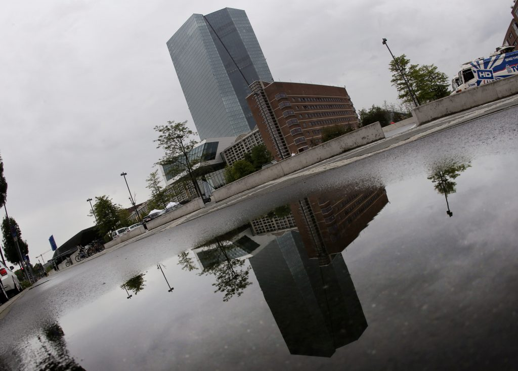The headquarters of the European Central Bank is reflected in a puddle in Frankfurt, Germany, Thursday, July 21, 2016. Later the day there will be a news conference following a meeting of the ECB governing council. (AP Photo/Michael Probst)