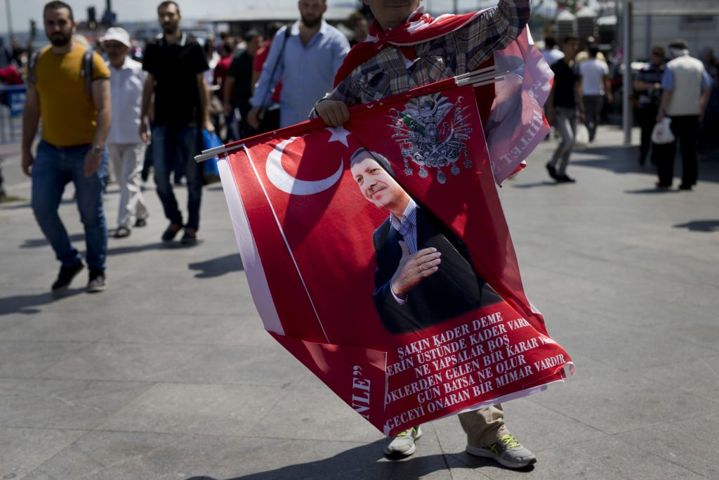 """A street vendor sells flags with Turkish President Recep Tayyip Erdogan in central Istanbul, Thursday, July 21, 2016. President Erdogan on Wednesday declared a three-month state of emergency following a botched coup attempt, declaring he would rid the military of the """"virus"""" of subversion and giving the government sweeping powers to expand a crackdown that has already included mass arrests and the closure of hundreds of schools. (AP Photo/Petros Giannakouris)"""