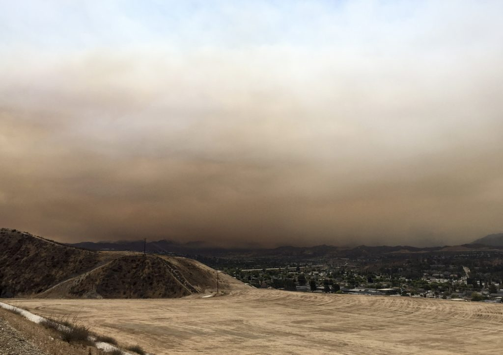 Heavy smoke from a wildfire is seen from Golden Valley Road and Five Knolls Drive Santa Clarita, Calif., on Saturday, July 22, 2016. The fire in northern Los Angeles County grew, darkening skies with smoke that spread across the city and suburbs, reducing the sun to an orange disk at times. The South Coast Air Quality Management District warned that at times air would reach unhealthy levels. The fire erupted Friday afternoon in the Sand Canyon area near State Route 14 as the region was gripped by high heat and very low humidity. (Katharine Lotze/The Santa Clarita Valley Signal via AP)