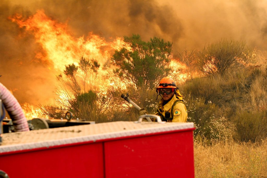 "Los Angeles County firefighters pause to fight the flames due to erratic winds in Placenta Caynon Road in Santa Clarita, Calif., Sunday, July 24, 2016. Flames raced down a steep hillside ""like a freight train,"" leaving smoldering remains of homes and warnings that more communities should be ready to flee the wildfire churning through tinder-dry canyons in Southern California, authorities said Sunday. (AP Photo/Matt Hartman)"