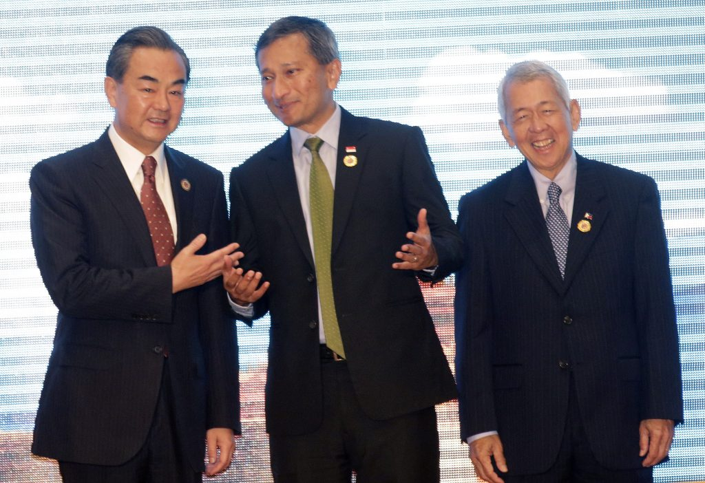 Chinese Foreign Minister Wang Yi, left, talks to Singapore's Foreign Minister Vivian Balakrishnan, center, and Philippine Foreign Secreatary Perfecto Yasay, during the Association of Southeast Asian Nations (ASEAN) –China Foreign Ministers' Meeting in Vientiane, Laos, Monday, July 25, 2016. A highly anticipated meeting between Southeast Asian foreign ministers and their Chinese counterpart Wang Yi has begun in what is expected to be tense discussions on China's territorial expansion in the South China Sea. (AP Photo/Sakchai Lalit)