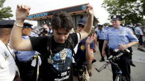 A demonstrator is taken into custody by Philadelphia Police after climbing over a barricade on Monday. (AP Photo/Matt Slocum)