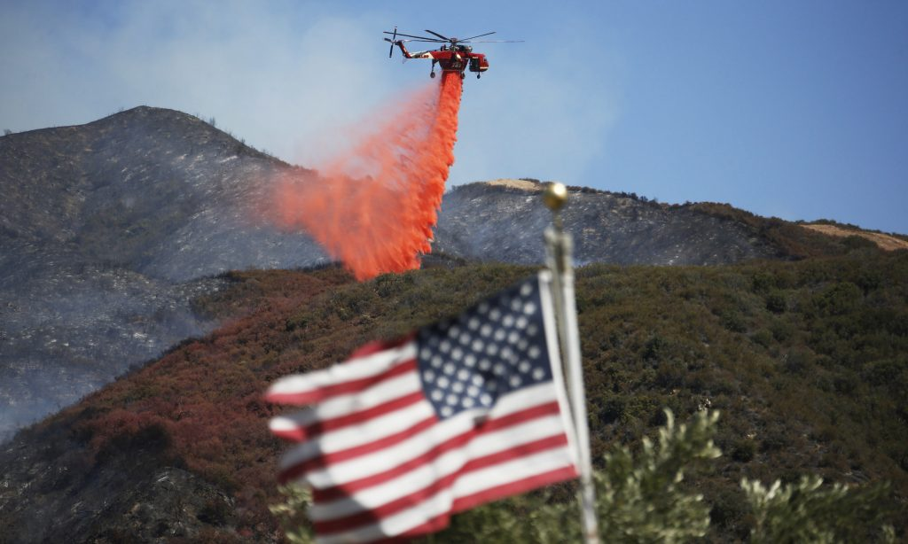 Framed by a burned-over hillside, rear, and an American flag in the foreground, a helicopter drops fire retardant ahead of advancing flames as a wildfire approaches Placerita Canyon in Santa Clarita, Calif., Monday, July 25, 2016. A raging wildfire that forced thousands from their homes on the edge of Los Angeles continued to burn out of control Monday as frustrated fire officials said residents reluctant to heed evacuation orders made conditions more dangerous and destructive for their neighbors. (AP Photo/Nick Ut)