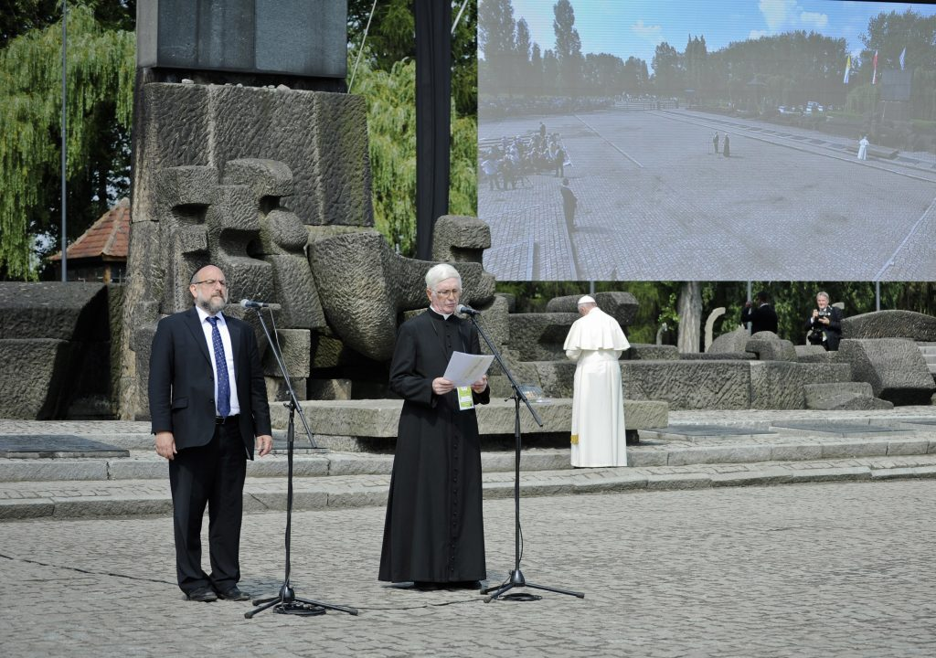 Pope Francis, right with back to camera, prays as Poland's chief rabbi Michael Schudrich, left, stands next to Rev. Stanislaw Ruszala, a priest from a village where the Nazis killed a Polish family because it was protecting Jews, as he reads a psalm in Polish during the papal visit to the site of the German Nazi death camp of Birkenau in Oswiecim, Poland. (Tomasz Pielesz/ Auschwitz Museum via AP)