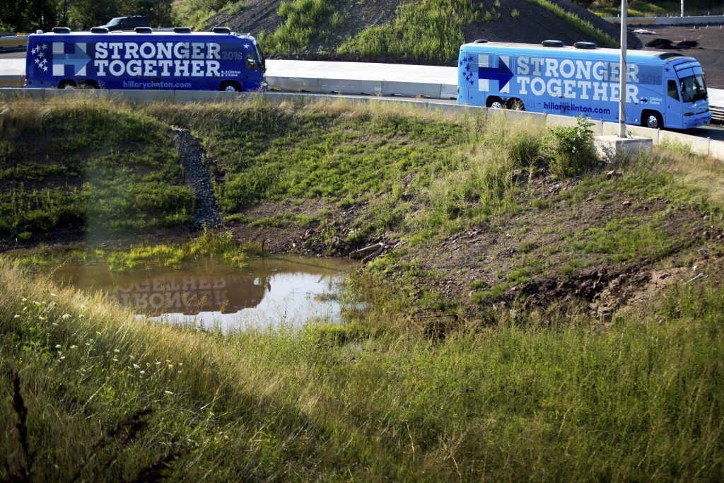 The campaign buses carrying Democratic presidential candidate Hillary Clinton and Democratic vice presidential candidate, Sen. Tim Kaine, D-Va., and their spouses, former President Bill Clinton and Anne Holton, depart from a rally at K'NEX, a toy company, in Hatfield, Pa., Friday, July 29, 2016, to travel to Broad Street Market in Harrisburg, Pa. Clinton and Kaine begin a three day bus tour through the rust belt. (AP Photo/Andrew Harnik)