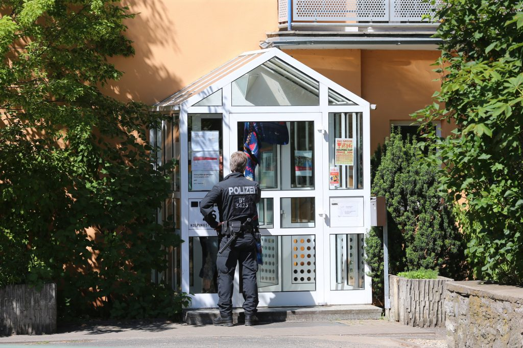 A police officer enters the Kolping House in Ochsenfurt, Germany, Tuesday July 19, 2016. On Monday evening a 17-year-old man from Afghanistan, attacked passengers with an ax and knife in a regional train near Wuerzburg, Germany. The attacker came to Germany over a year ago as an unaccompanied minor and applied for asylum in March of last year. He lived in that home for young refugees in Ochsenfurt near Wuerzburg until two weeks ago when he was placed with a foster family in the same town, The attacker was shot and killed by police as he fled. (Karl-Josef Hildenbrand/dpa via AP)