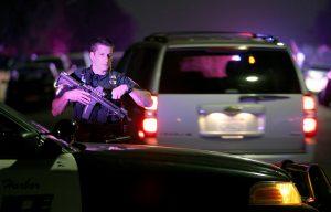 A San Diego Harbor Police officer helps to secure the scene near where two San Diego Police officers were shot on Thursday night. (John Gastaldo/The San Diego Union-Tribune via AP)