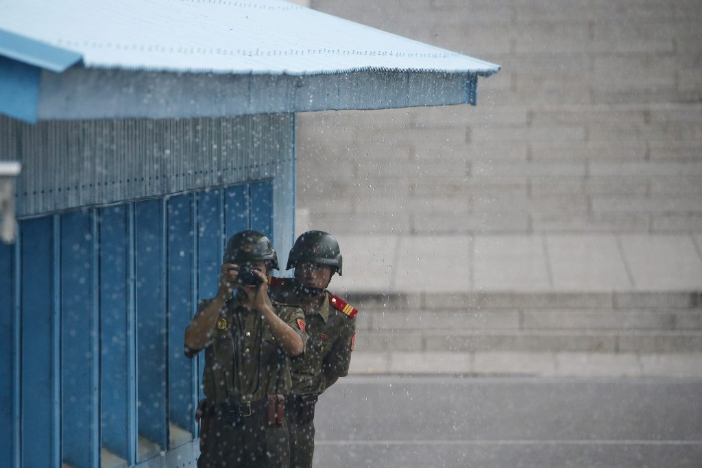 North Korean soldiers keep a watch toward the south as it rains during a ceremony marking the 63rd anniversary of the signing of the Korean War cease-fire armistice agreement at the truce village of Panmunjom, South Korea, Wednesday, July 27, 2016. (Kim Hong-Ji/Pool Photo via AP)