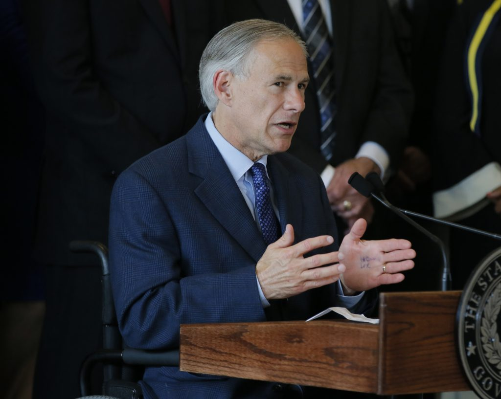 Texas Gov. Greg Abbott, right, responds to questions about the police shootings during a news conference at City Hall, Friday, July 8, 2016, in Dallas. Five police officers are dead and several injured following a shooting during what began as a peaceful protest in the city the Thursday night. (AP Photo/Tony Gutierrez)