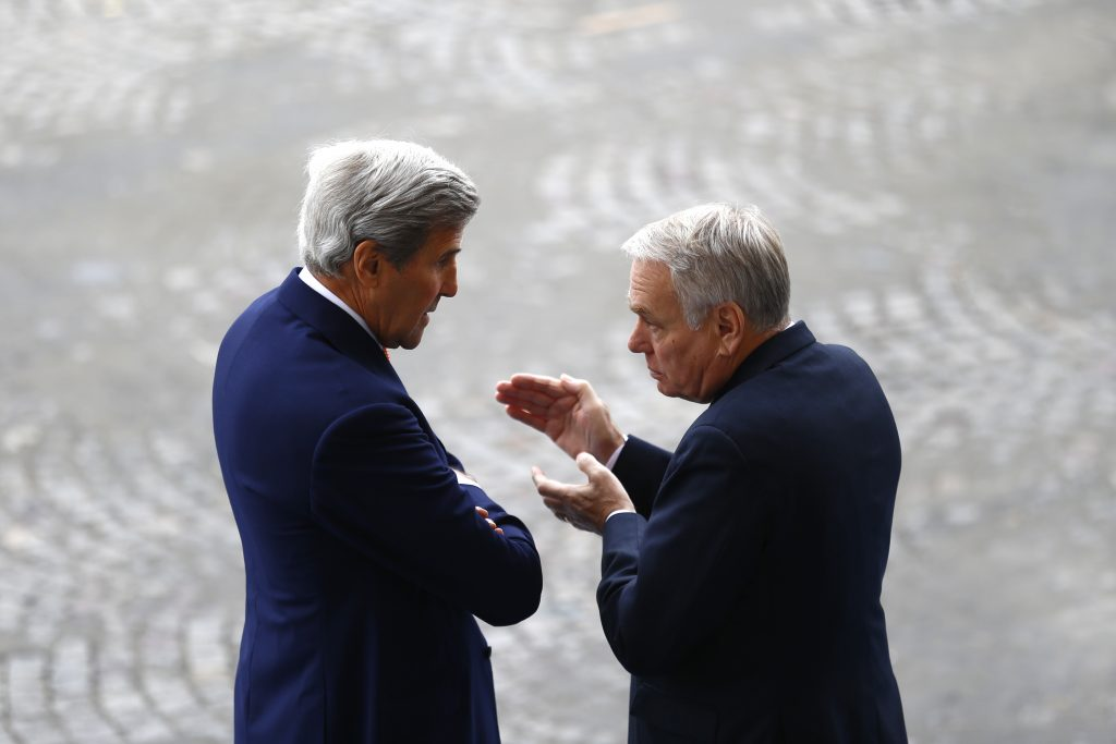 U.S Secretary of State John Kerry, left, listens to French Foreign Minister Jean-Marc Ayrault on the Champs Elysees avenue before the Bastille Day Parade in Paris, Thursday, July 14, 2016. (AP Photo/Francois Mori)