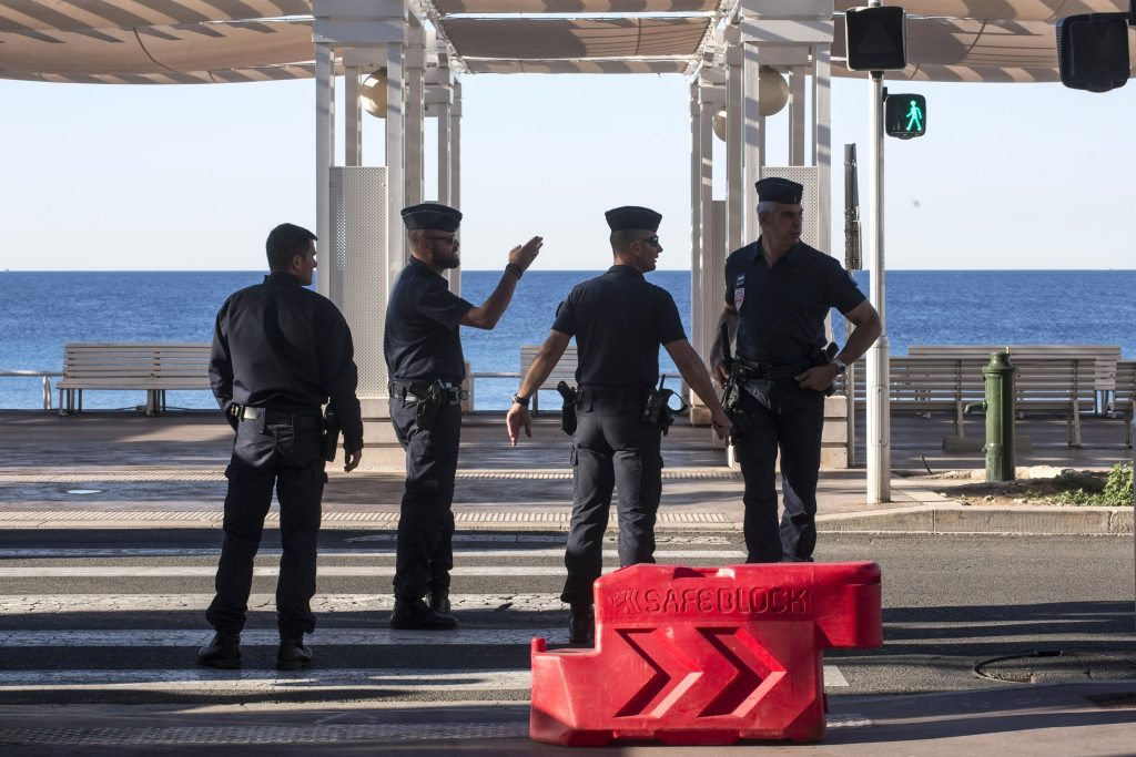 Riot police officers patrol on the Promenade des Anglais in Nice, southern France, Saturday, July 16, 2016. Nice's seaside boulevard reopens to traffic Saturday following a dramatic truck attack which killed more than 80 people and wounded more than 200 others at a fireworks display. (AP Photo/Laurent Cipriani)