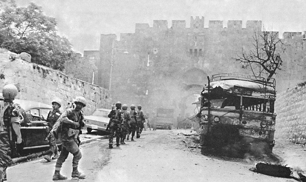 A column of soldiers moves past a burned out bus as paratroopers force open the Lion's Gate in Yerushalayim during the Six Day War, June 1967.  (AP Photo)