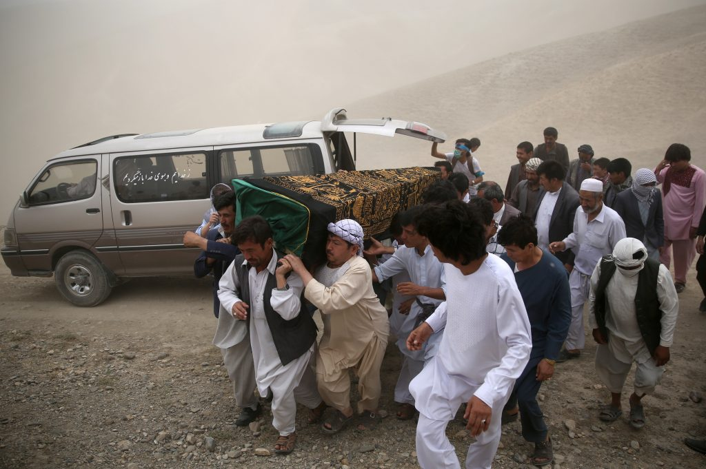 Afghan men carry the coffin of a victim who died from a suicide attack, in Kabul, Afghanistan, on Sunday. (AP Photos/Massoud Hossaini)