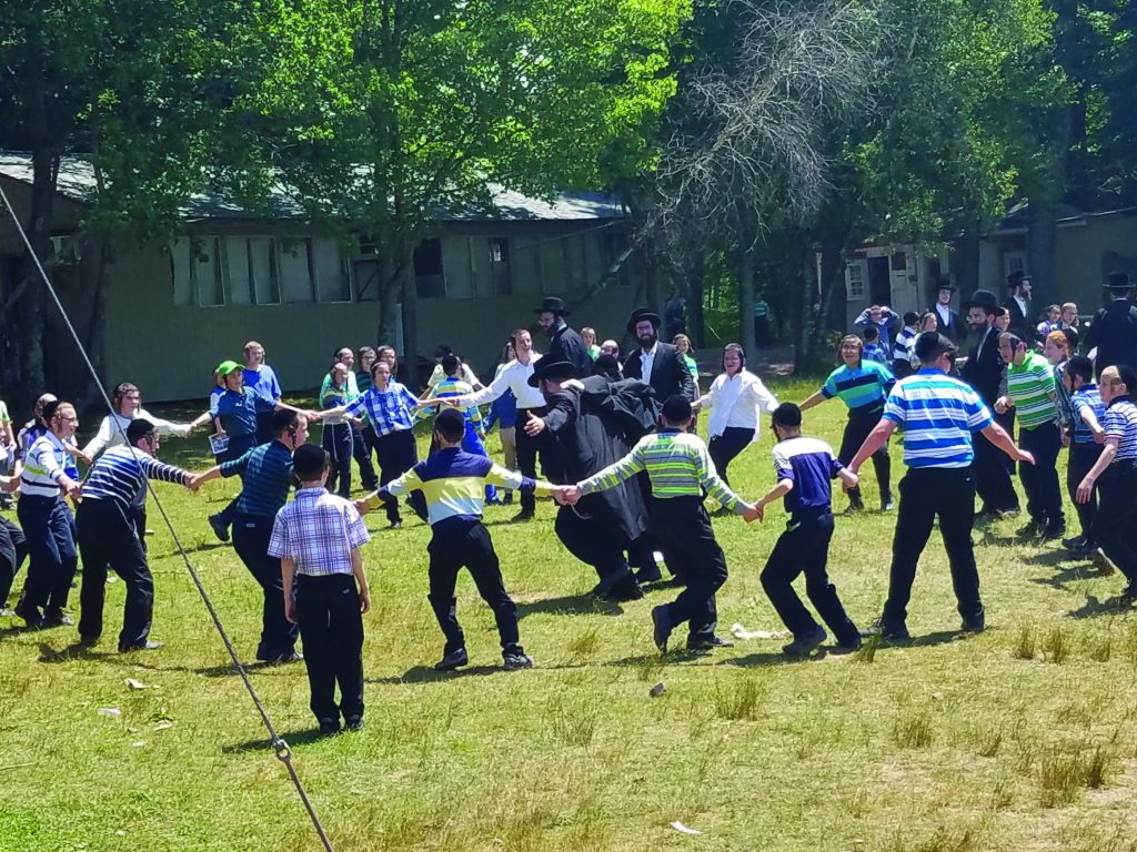 Campers and staffers at the Klausenburger camp dance on Friday in thanks to Hashem that a potentially dangerous bus accident earlier that morning ended in relatively minor injuries. (Megahetz)