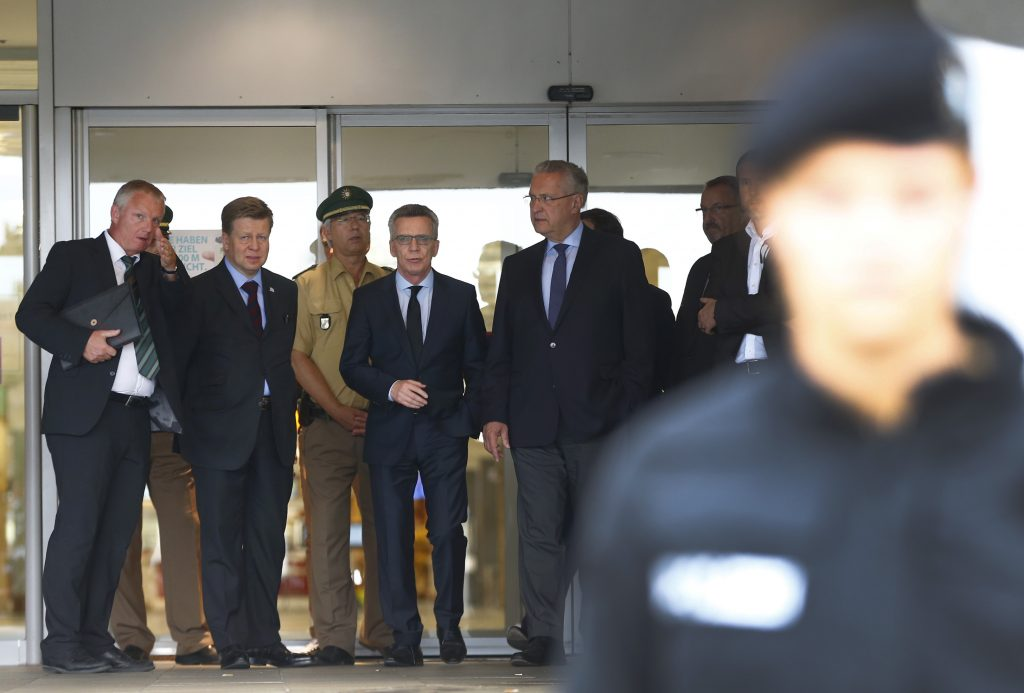 German Interior Minister Thomas De Maiziere (4th L) leaves after visiting the Olympia shopping mall, where yesterday's shooting rampage started, in Munich, Germany July 23, 2016. REUTERS/Arnd Wiegmann