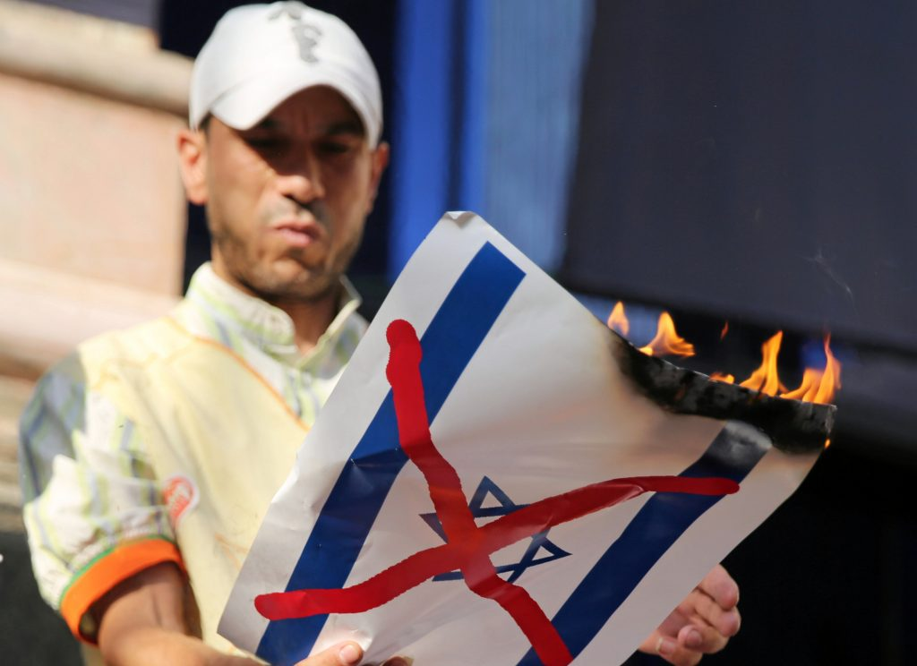 A demonstrator burns an Israeli flag placard in front of the journalists' syndicate in Cairo to protest the recent visit to Israel by Egyptian Foreign Minister Sameh Shoukry, in Cairo, Wednesday. (Reuters/Mohamed Abd El Ghany)