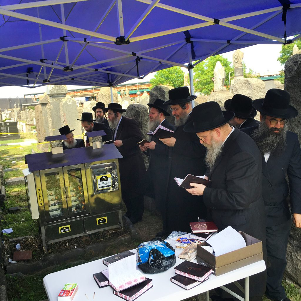 "Yidden davening at the tziyun of Harav Yaakov Ehrenreich, zt""l, at Washington Cemetery in Boro Park, on Monday, 28 Sivan, his 114th yahrtzeit."
