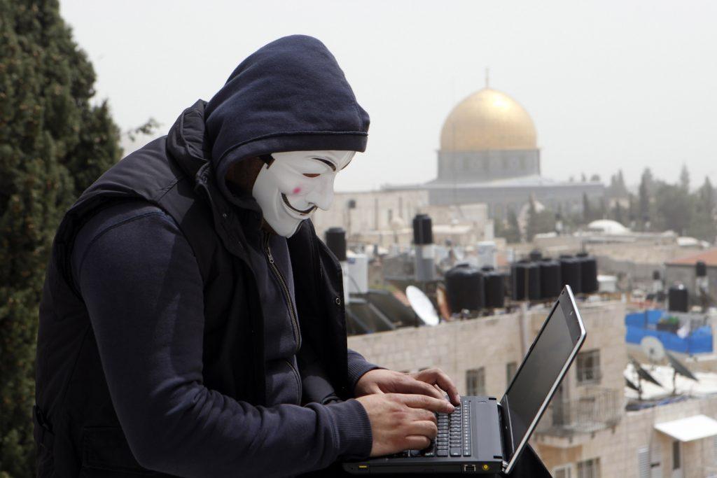 A Palestinian youth wearing masks used by computer hackers who attacked a number of Israeli websites recently, seen backdropped by the DOme of the Rock, in Jerusalem's Old City. April 08 2013. Photo by Sliman Khader/FLASH90 *** Local Caption *** îñëä àðåðéîåñ äà÷ø îñéëä
