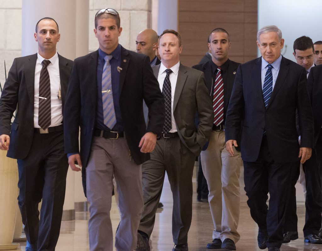 Prime Minister Binyamin Netanyahu, surrounded by security and personnel, arrives at a Likud meeting in the Knesset in this 2014 photo. To his right is his chief of staff, Ari Harrow. (Miriam Alster/Flash90)