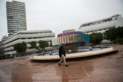 A man carrying an umbrella walks on Dizengoff square in Tel Aviv, on a rainy day. November 17, 2015. Photo by miriam Alster/FLASH90