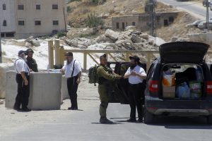 Israeli soldiers put on tefillin at a checkpoint at the entrance to Yatta, near Chevron, on Sunday.(Wisam Hashlamoun/Flash90)