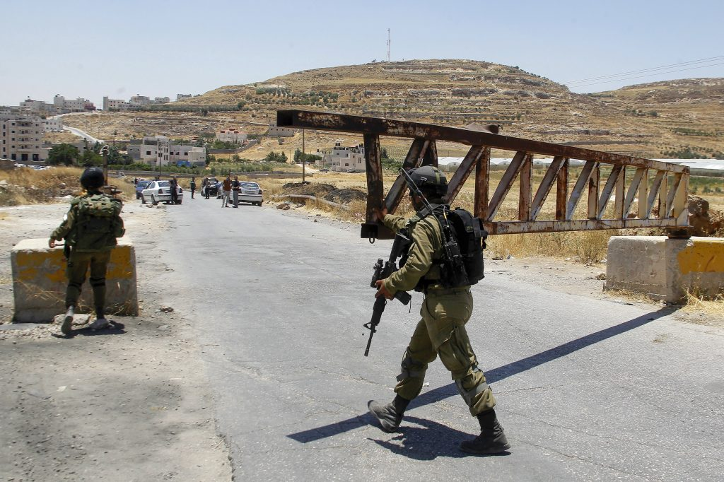 Israeli soldiers guard a checkpoint at the entrance to Yatta, near Chevron, on Sunday.(Wisam Hashlamoun/Flash90)