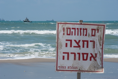 """A sign reading """"Polluted water, batheing forbidden"""" seen in the sea at Haifa Bay, due to an oil spill. Photo by Doron Golan/FLASH90"""